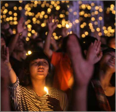 Candlelight worship in an Indonesian stadium.