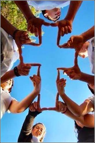 Kids making shape of a cross with their fingers.